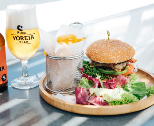 French fries, iced cold beer, a fresh salad and a juicy burger served on a tray.